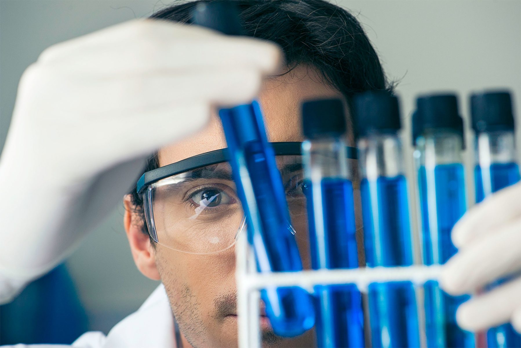 A man in gloves and goggles looking closely at several test tubes containing blue liquid.